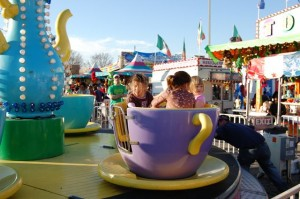 Tiller rides the teacups with the big girls.