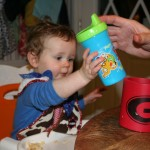 Show baby how sippy cup fits into coozie.
