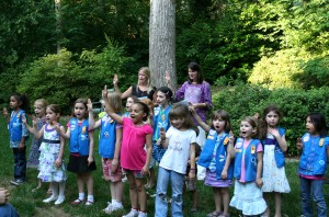 Doing the girl scout pledge thingie with the three fingers. Tiller is beside the kid in the pink shirt.