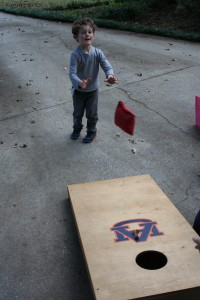 Boys focused on cornhole and that jumpie thing.