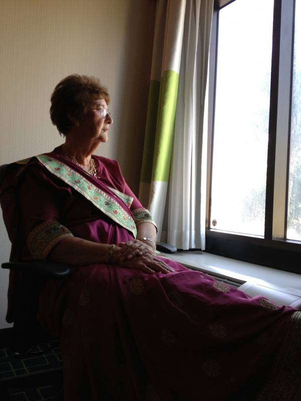 My mother-in-law, pensive at a hotel window while they wedding party dresses.